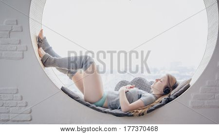 Blond Girl In Casual Clothes And Wool High Socks Lying On A Round Window Sleeping And Listening To M