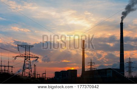 Industrial power plant with smokestack during sunset