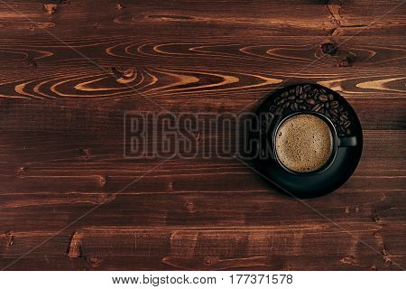 Hot coffee in black cup with crema and beans with copy space on brown old wooden board background top view. Rustic style.