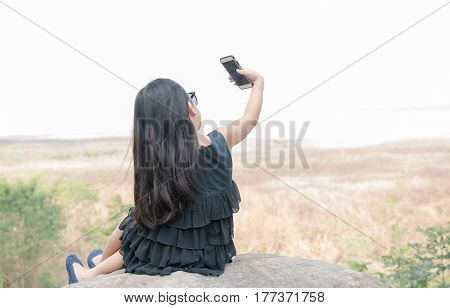 Nature outdoor technology social concept. cute girl holding smartphone to taking selfie. Young child in park takes picture of herself on nature background.