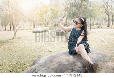 Nature outdoor technology social concept. cute girl taking selfie. Young child in park takes picture of herself on nature background.