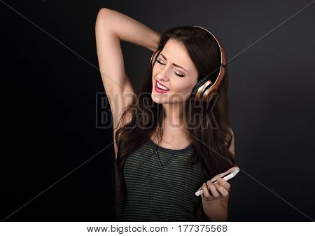 Beautiful Singing Young Woman Listening The Music In Wireless Headphone And Holding Mobile Phone On