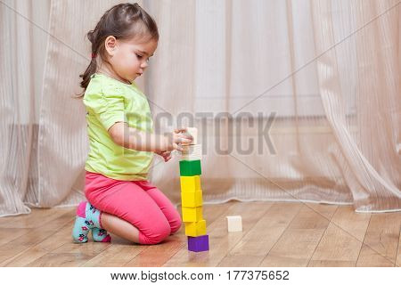 Cute little child girl sitting on the floor and playing with building blocks