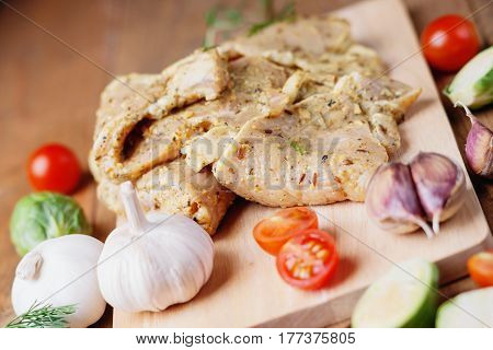 Raw marinated pork meat and vegetables on a wooden cutting board
