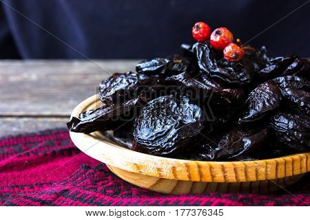 Prunes in a wooden plate on a dark background