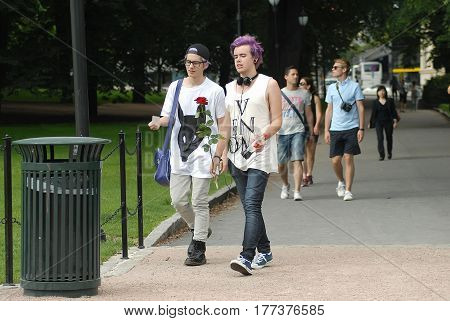 Oslo Norway - July 22 2014: two young stylish friends walking in the park and talking near the Royal Palace in Oslo.