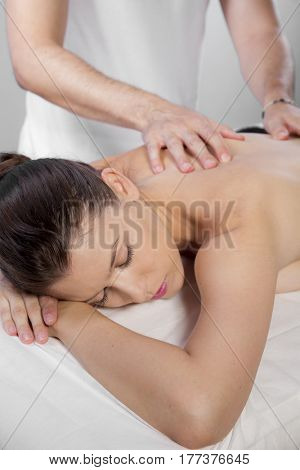 Massage and relaxation, beautiful brunette woman relaxing on a stretcher receiving a therapeutic massage from hands of a professional masseuse