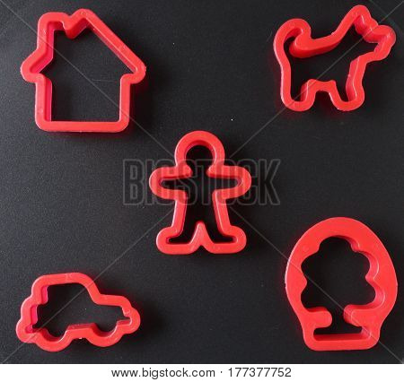set of molds for plasticine. Toy pie mould on  black background. icons in the form of man, house, dog, car and tree.
