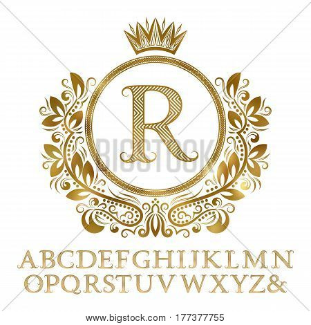 Golden patterned letters with initial monogram in coat of arms form. Shining font and elements kit for logo design.