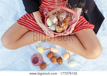 Close up portrait of woman holding easter basket full of painted eggs while sitting with legs crossed