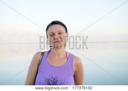 Happy middle-aged brunette woman. Lake in the background