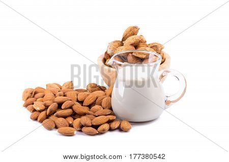 Glass of Almond milk with a heap of almonds on white background.
