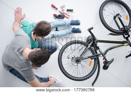 Overhead View Of Father And Son Sitting Near Bicycle On White