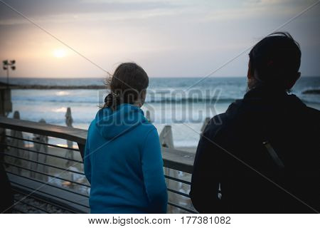 Sunset on the Mediterranean Sea. Middle-aged woman and her daughter girl teenager on the waterfront back to the photographer