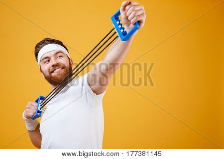 Close up portrait of a cheerful sportsman doing fitness exercises with expander over orange background