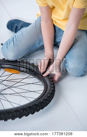 Little Boy Repairing Bicycle Tire In Studio On White