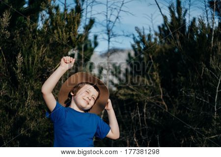 Happy Smiling boy outdoor in summer forest. 6 years old kid in hat playing in nature. Copy space