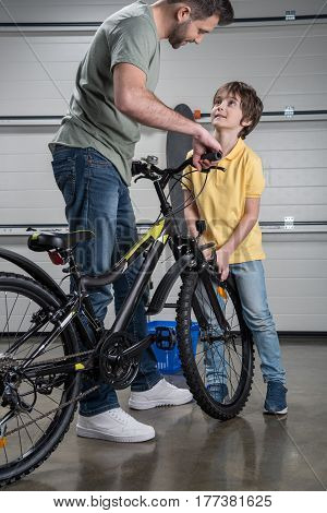 Smiling Father And Son Standing With Bicycle And Looking At Each Other