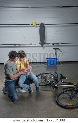 Father Putting Medical Patch On Hand Of Son Falling Off Bike
