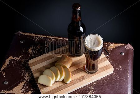 Glass And Bottle Of Dark Beer With Smoked Cheese On Cutting Board.