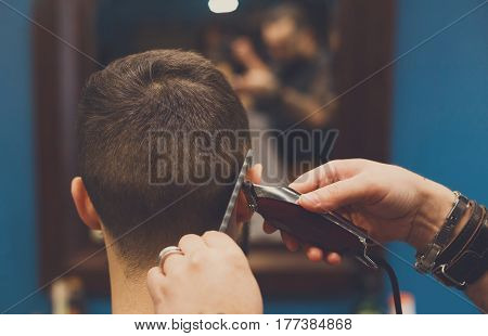 Barber make haircut with trimmer hair clipper in barbershop, closeup of client's head. Hairstyle in male hair salon