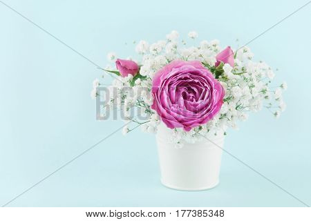 Beautiful pink rose flower and gypsophilla in white vase on turquoise vintage table.