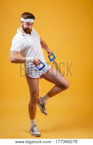 Full length portrait of a fitness man workout with expander over orange background
