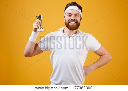 Image of happy young sportsman holding reward dressed in white t-shirt standing isolated over yellow background. Looking at camera.