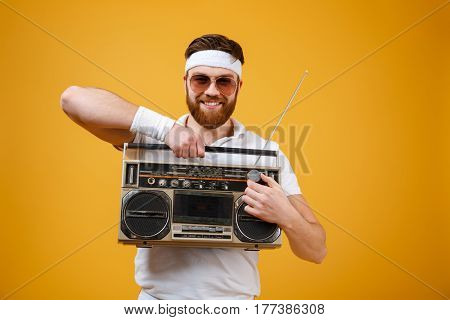 Image of cheerful young man wearing sunglasses holding tape recorder dressed in white t-shirt isolated over yellow background. Looking at camera.