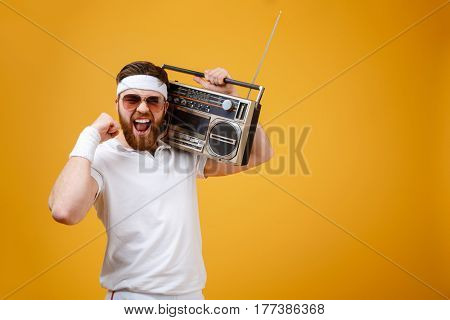 Image of screaming young man wearing sunglasses holding tape recorder dressed in white t-shirt isolated over yellow background. Looking at camera make winner gesture.