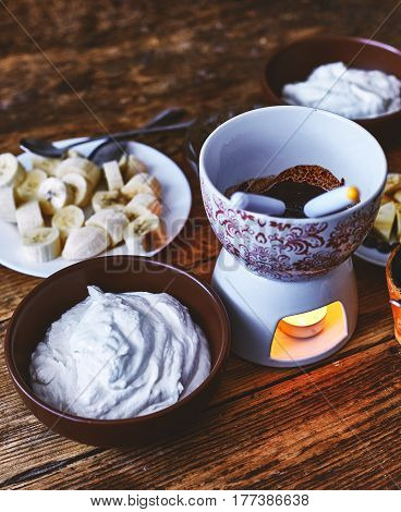 dieting cottage cheese with fresh bananas, Fondue with chocolate on a dark old wooden table. Table setting for two. view from above