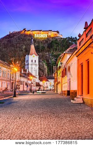 Rasnov Romania. Evening twilight with medieval saxon city in Transylvania and hilltop ruins of the fortress.