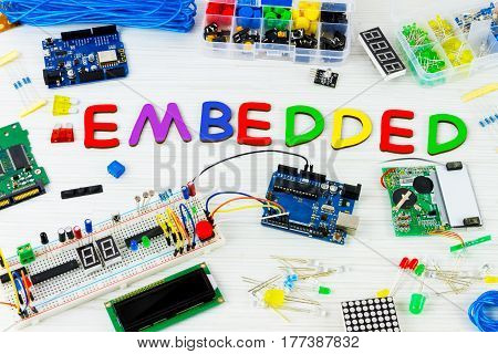 Microcontrollers chips resistors and light-emitting diodes on white desktop of hardware engineer. Colorful letters connected together to word