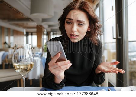 Displeased Woman in dress which sitting by the table in restaurant and looking at phone