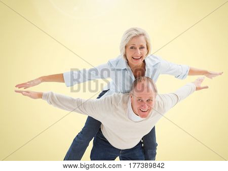 Digital composite of Happy Senior Couple having Fun against a yellow background