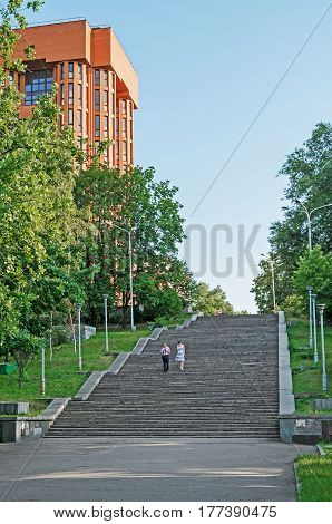 Dnipro Ukraine - July 05 2013: In summerly evening pedestrians go on foot the stairs of city park