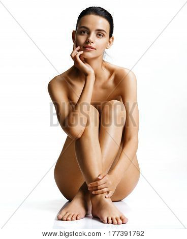Naked woman with perfect skin sitting on white background. Photo of beautiful woman with gorgeous figure. Wellness and Spa concept
