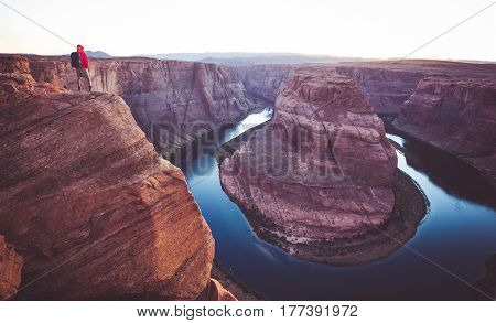 A male hiker is standing on steep cliffs enjoying the beautiful view of Colorado river flowing at famous Horseshoe Bend overlook in beautiful post sunset twilight on a summer evening Arizona USA