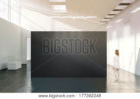 Woman stand near blank black wall mockup in modern white gallery. Girl walk near dark big stand mock up in museum with contemporary art exhibitions. Large hall interior grey banner exposition