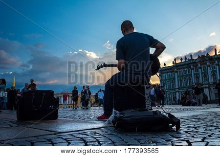 People Enjoy The Art Of Street Musician In The Palace Square, St. Petersburg, Russia