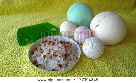 Toiletries bath soap, bath salt and bath bombs of different sizes on a yellow towel