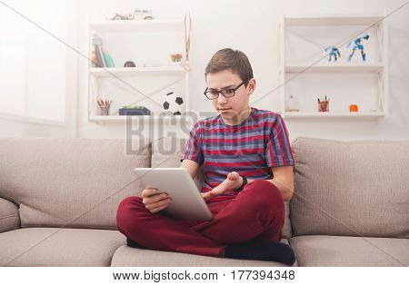 Gadgets and technology concept - teenage boy using digital tablet, watching football on portable device, playing online game while sitting on the couch in living room at home
