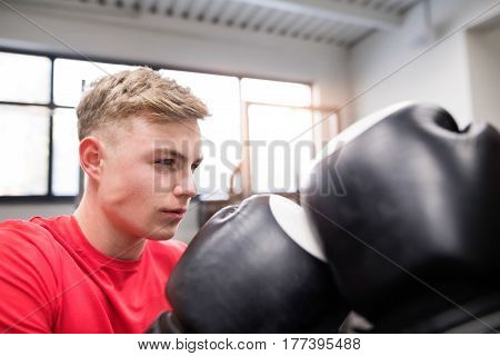 Fit handsome man boxing with his unrecognizable rival. Two athlete boxers wearing boxing gloves sparred in boxing gym.