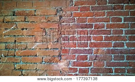 Part of the old brick wall of red-brown color with a vertical stripe along the middle of the photo.