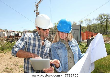 Engineers on construction site with plan