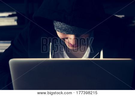 hacker in hoodie using laptop for cyber crime