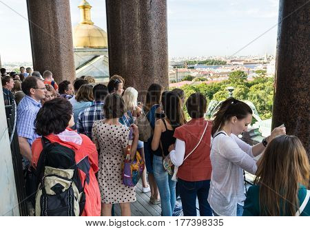 ST. PETERSBURG RUSSIA - JULY 14 2016: Tourists admire the view of St. Petersburg on the upper colonnade of St. Isaac's Cathedral