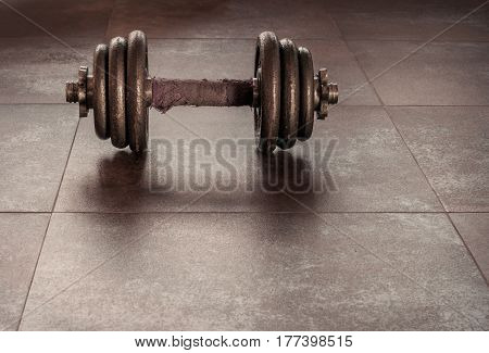 Dumbbell old laying on the ground.In a lonely atmosphere