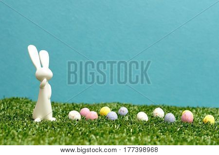 A white plastic bunny figurine displayed with speckled easter eggs