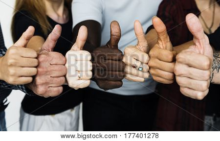 Group of people thumbs up together